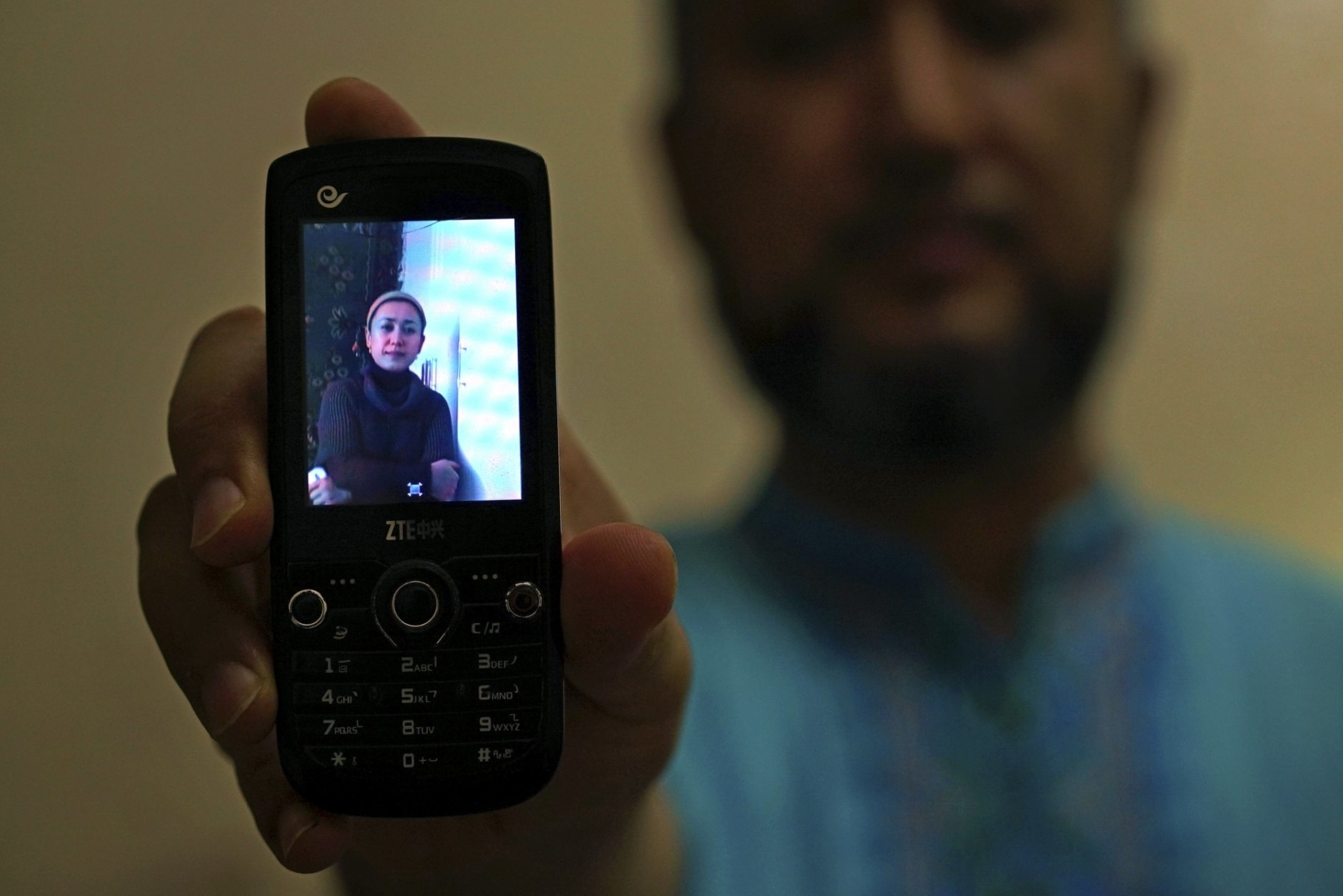 """In this Aug. 24, 2018, photo, Halmurat Idris holds up a picture of his elder sister on his phone at his home in Istanbul, Turkey. Idris says his sisters were monitored as part of a government homestay program, part of a broader crackdown on religious expression in China's far western region of Xinjiang. While in exile in Turkey, he had spotted a picture of his ethnic Uighur sister and an elderly woman of China's Han majority together, with the caption declaring that his sister had found a """"Han Chinese mother"""". (AP Photo/Dake Kang)"""
