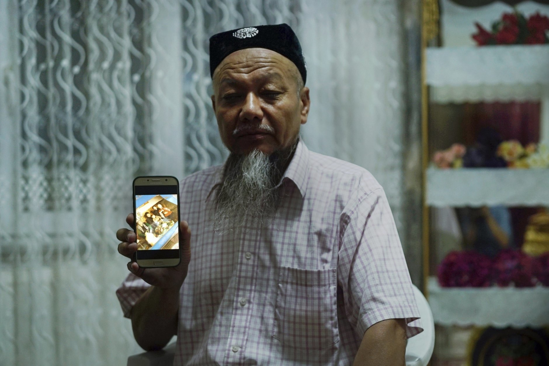 In this Aug. 22, 2018, photo, Ablikim Abliz holds up his phone displaying a photo of his uncle's family with an unknown Han Chinese man in Istanbul, Turkey. Abliz heard the Han Chinese man was part of a government homestay program meant to monitor his relatives, part of a broader crackdown on religious expression in China's far western region of Xinjiang. He later heard that his uncle's front door was boarded up and sealed with police tape, and has not been able to contact them since. (AP Photo/Dake Kang)