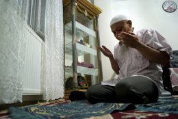 In this Aug. 22, 2018, photo, Ablikim Abliz prays at his home in Istanbul, Turkey. Abliz was sent a picture of his uncle's family with a Han Chinese man in the background, who he heard was part of a government homestay program in China's far western region of Xinjiang meant to monitor his relatives. (AP Photo/Dake Kang)
