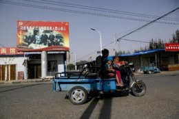 FILE - In this Sept. 20, 2018, file photo, an Uighur woman shuttles school children on an electric scooter as they ride past a propaganda poster showing China's President Xi Jinping joining hands with a group of Uighur elders in Hotan, in western China's Xinjiang region. Under Chinese President Xi Jinping, the Uighur homeland has been blanketed with stifling surveillance, from armed checkpoints on street corners to facial-recognition-equipped CCTV cameras steadily surveying passers-by. Now, Uighurs say, they must live under the watchful eye of the ruling Communist Party even inside their own homes. (AP Photo/Andy Wong, File)