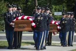 In this Sept. 6, 2018 photo, the 3rd Infantry Regiment, also known as the Old Guard, carry the remains of two unknown Civil War Union soldiers to their grave at Arlington National Cemetery in Arlington, Va. The U.S. Army is being criticized for reburying the remains of two recently discovered Civil War soldiers without conducting DNA testing. The soldiers were found at Manassas National Battlefield, among severed limbs in what researchers believe was a surgeon's pit. Army officials said DNA testing was unjustified and reburied them as unknown soldiers at Arlington National Cemetery.  (AP Photo/Cliff Owen)