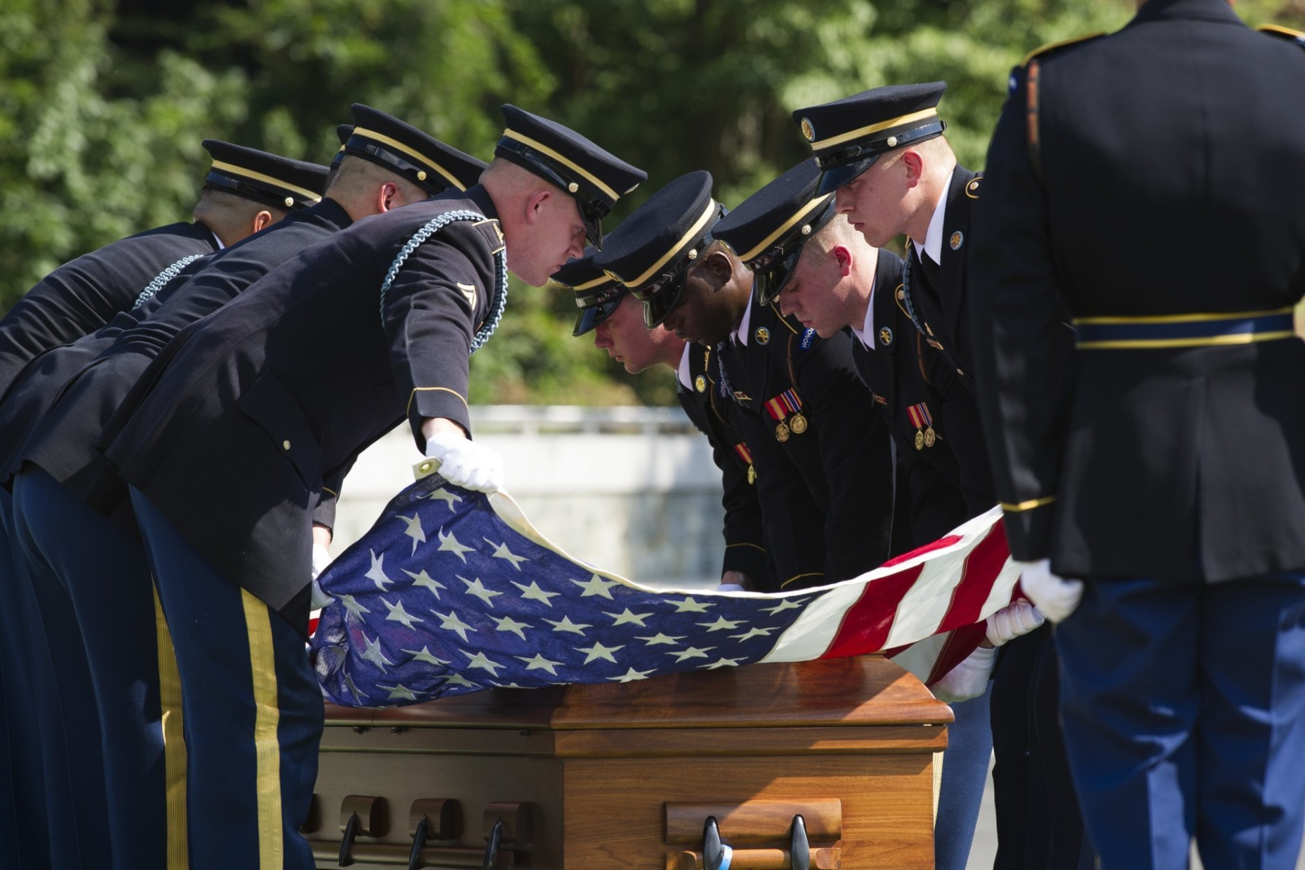 In this Sept. 6, 2018 photo, the 3rd Infantry Regiment, also known as the Old Guard, stretch the American flag over the casket containing the remains of one of two unknown Civil War Union soldiers at their grave at Arlington National Cemetery in Arlington, Va. The U.S. Army is being criticized for reburying the remains of two recently discovered Civil War soldiers without conducting DNA testing. The soldiers were found at Manassas National Battlefield, among severed limbs in what researchers believe was a surgeon's pit. Army officials said DNA testing was unjustified and reburied them as unknown soldiers at Arlington National Cemetery.  (AP Photo/Cliff Owen)
