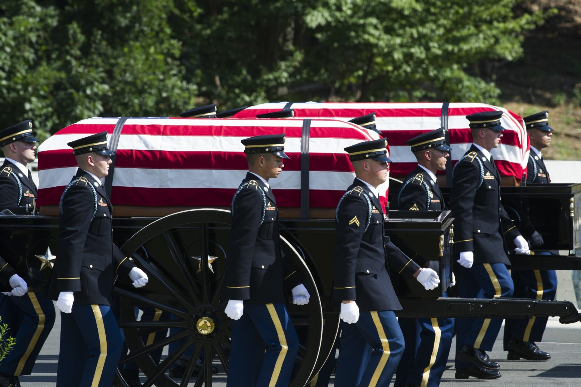 In this Sept. 6, 2018 photo, the 3rd Infantry Regiment, also known as the Old Guard, Caisson Platoon carry the remains of two unknown Civil War Union soldiers to their grave at Arlington National Cemetery in Arlington, Va.  The U.S. Army is being criticized for reburying the remains of two recently discovered Civil War soldiers without conducting DNA testing. The soldiers were found at Manassas National Battlefield, among severed limbs in what researchers believe was a surgeon's pit. Army officials said DNA testing was unjustified and reburied them as unknown soldiers at Arlington National Cemetery.  (AP Photo/Cliff Owen)