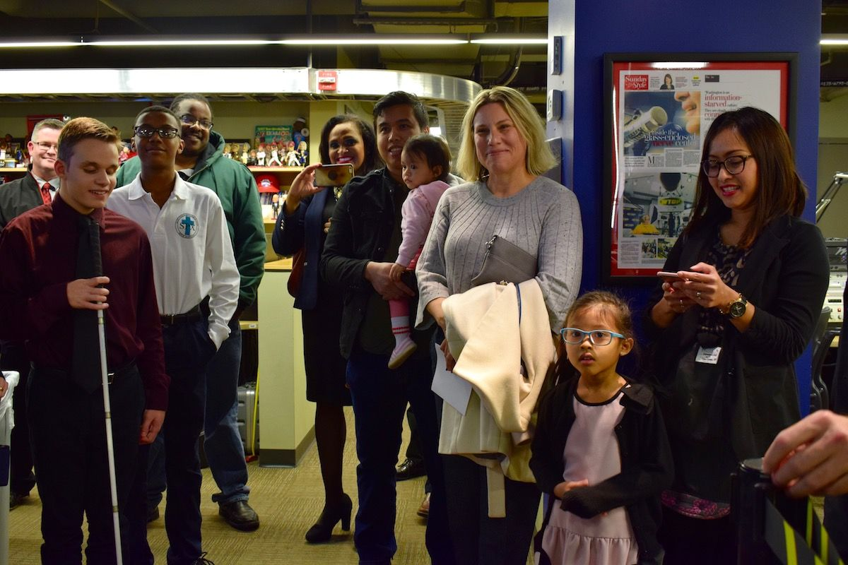 The contest winners get the rundown on the newsroom with their family members and some school officials. (WTOP/Teta Alim)
