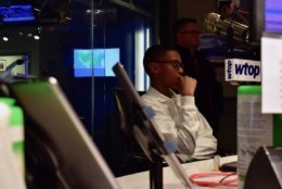 Sylvestre watches WTOP afternoon anchor Shawn Anderson deliver breaking news. (WTOP/Teta Alim)