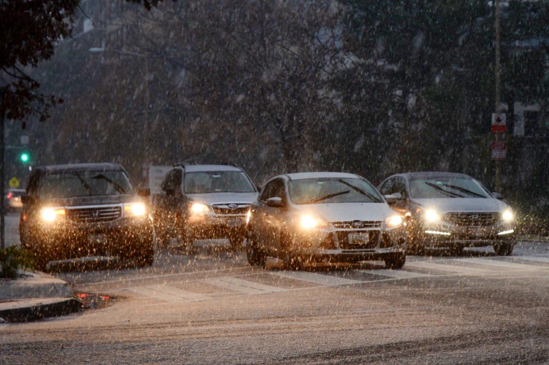 Cars wait at a traffic light in Northwest D.C. as snow falls. (WTOP/Dave Dildine)
