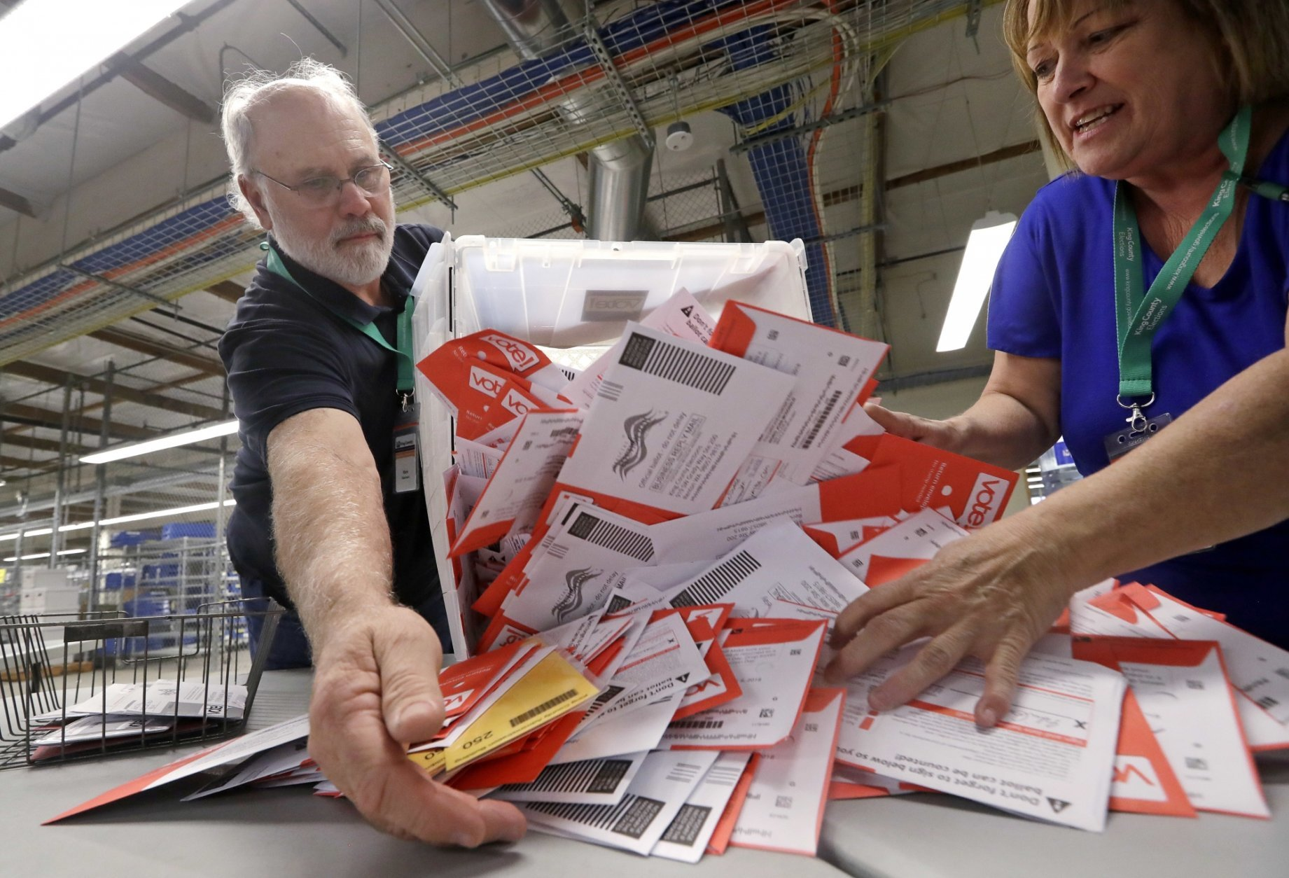 Election workers Mark Bezanson, left, and Julie Olson dump ballots collected earlier in the day from drop boxes onto a table for sorting at the King County Elections office, Monday, Nov. 5, 2018, in Renton, Wash. Voters in Washington all vote only by mail. (AP Photo/Elaine Thompson)