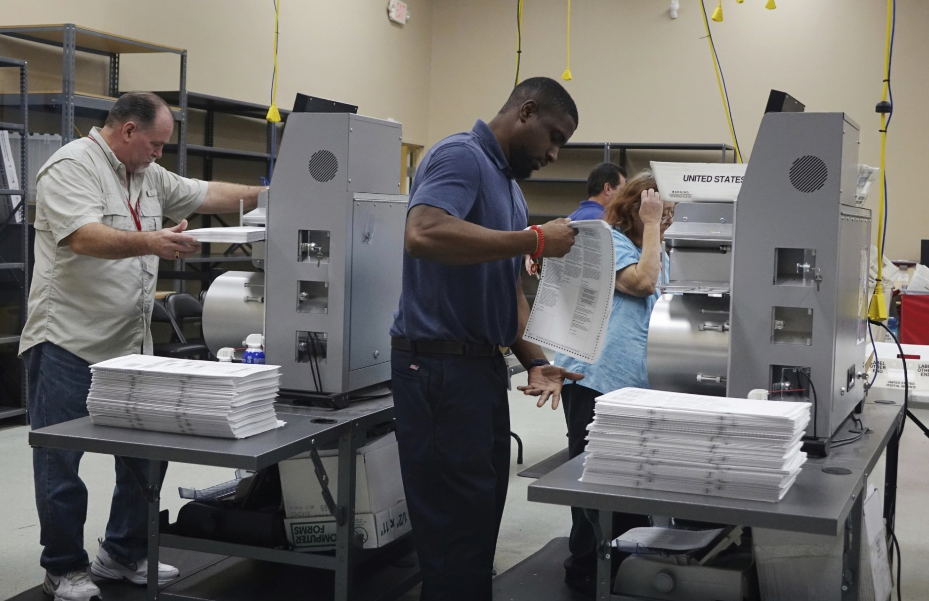 Election workers place ballots into electronic counting machines, Sunday, Nov. 11, 2018, at the Broward Supervisor of Elections office in Lauderhill, Fla. The Florida recount began Sunday morning in Broward County. (Joe Cavaretta /South Florida Sun-Sentinel via AP)