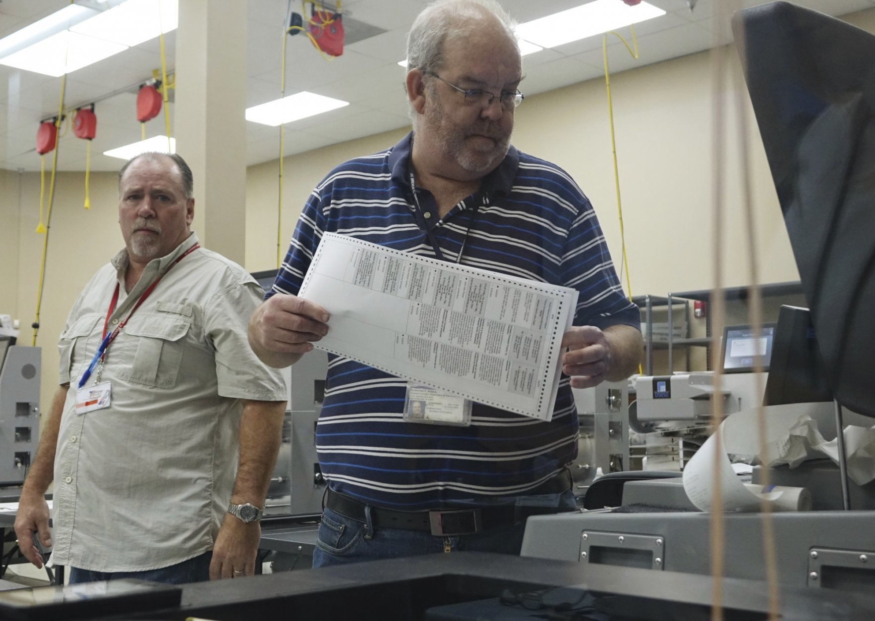 Election workers place ballots into electronic counting machines, Sunday, Nov. 11, 2018, at the Broward Supervisor of Elections office in Lauderhill, Fla. The Florida recount began Sunday morning in Broward County. (Joe Cavaretta/South Florida Sun-Sentinel via AP)