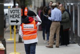 An election official, left, maintains the crowd line and parking spaces as people line up to vote at the Minneapolis Early Vote Center on the last day of early voting Monday, Nov. 5, 2018, in Minneapolis. The Associated Press will debut a new survey of the nation's electorate that aims to more accurately capture the story of how Americans vote and why in Tuesday's midterm elections. (AP Photo/Jim Mone)