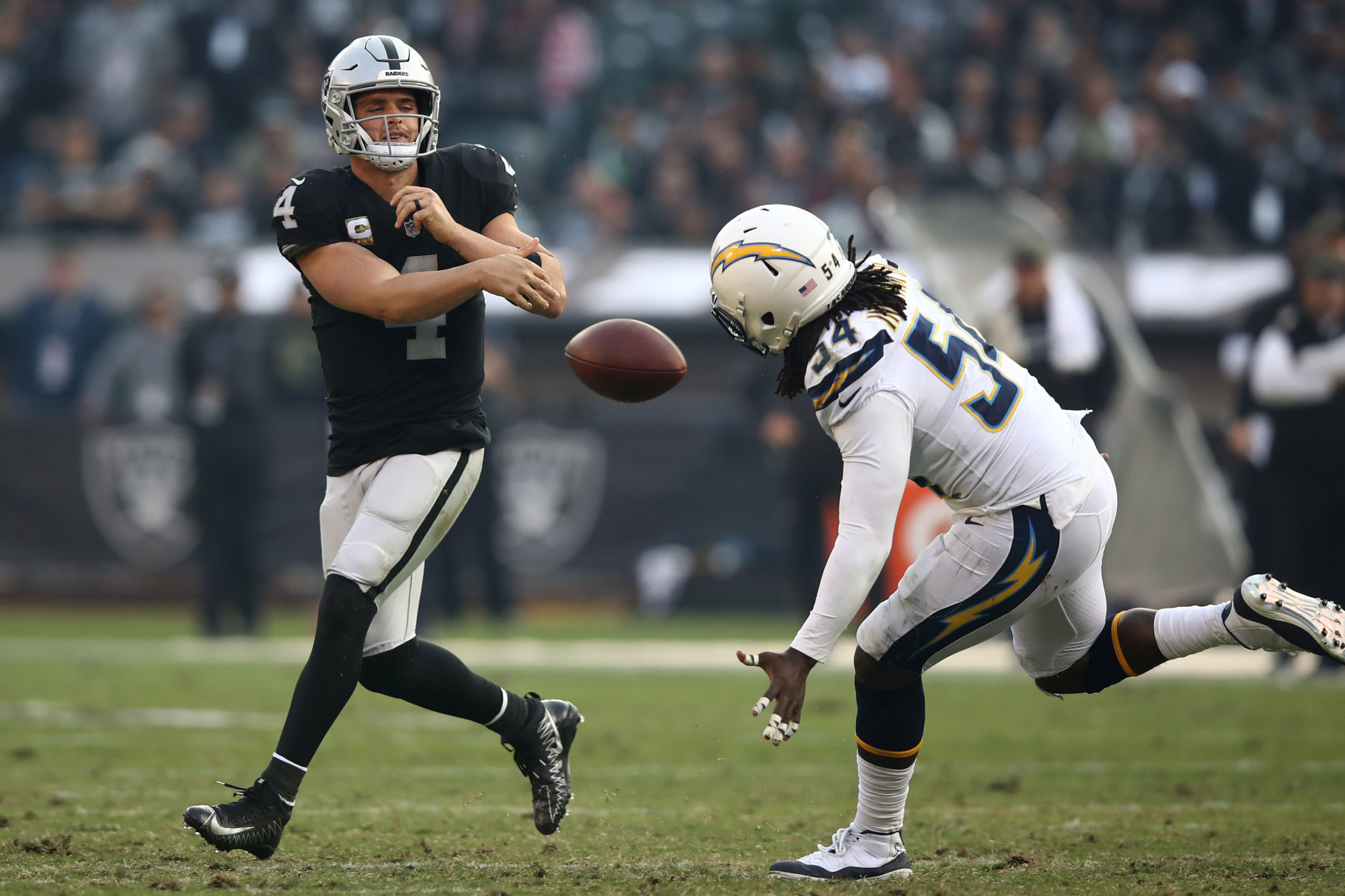 OAKLAND, CA - NOVEMBER 11: Derek Carr #4 of the Oakland Raiders throws the ball into the ground on fourth down during their NFL game against the Los Angeles Chargers at Oakland-Alameda County Coliseum on November 11, 2018 in Oakland, California. (Photo by Ezra Shaw/Getty Images)