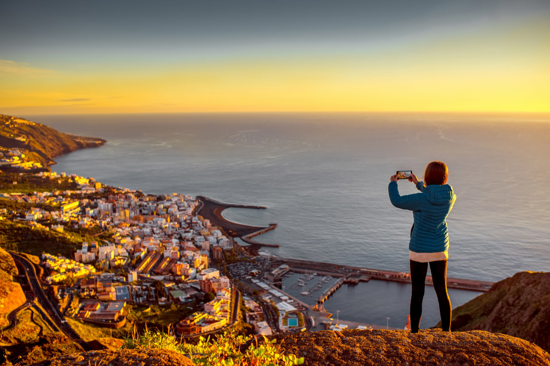 Young female traveler in blue jacket photographing Santa Cruz city standing on the top of the mountain on La Palma island in the morning