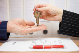 real estate seller is giving keys to buyer after signed deal