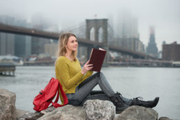 Young beautiful student girl reading a book sitting near New York City skyline. Study in USA university concept.