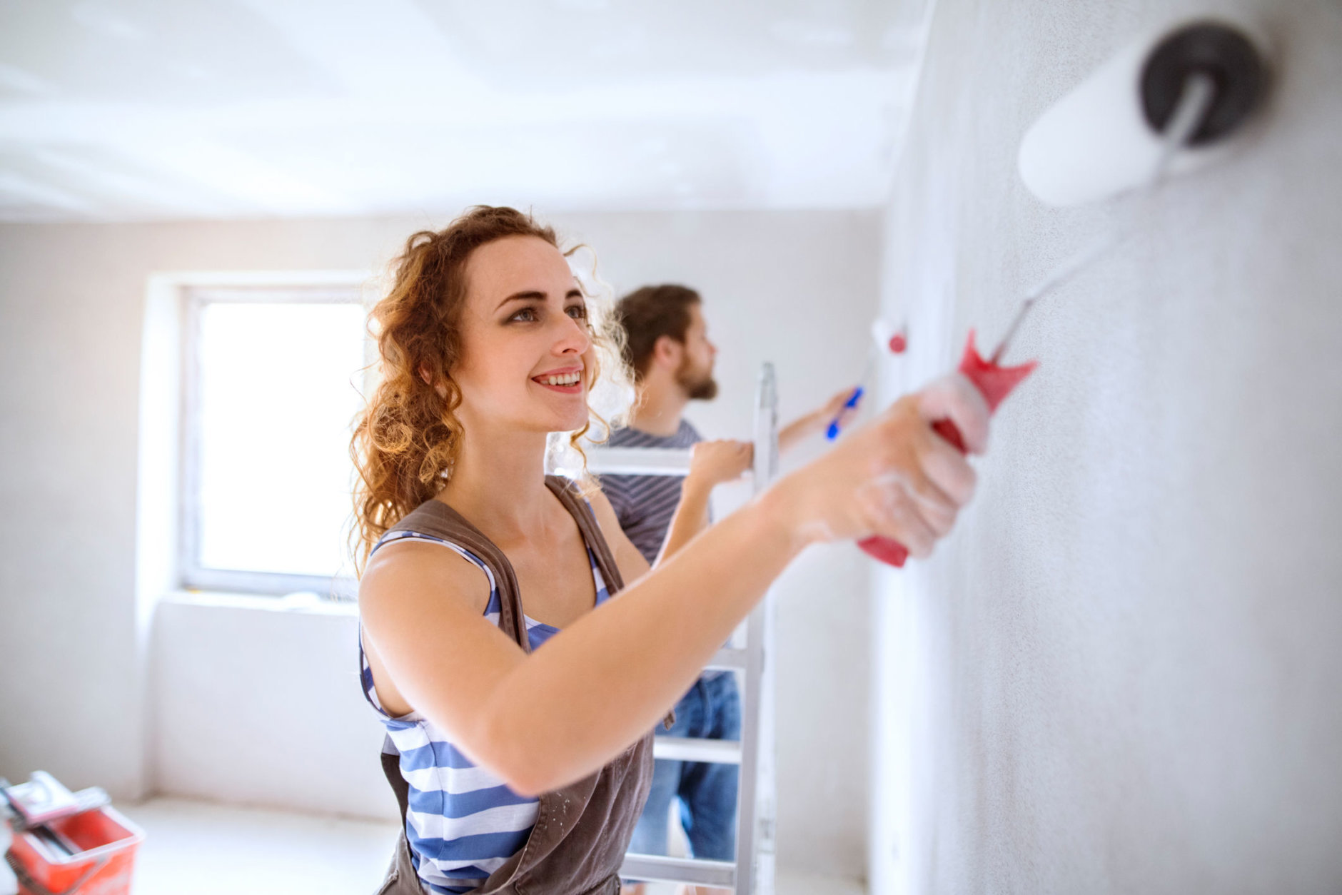 Beautiful young couple having fun and painting walls using paint rollers in their new house. Home makeover and renovation concept.