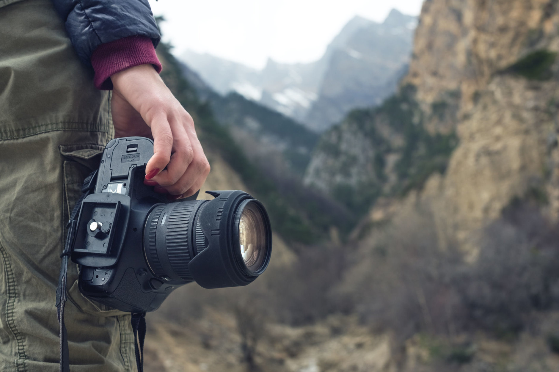 A female hand holds a camera against a caucasian mountain landscape