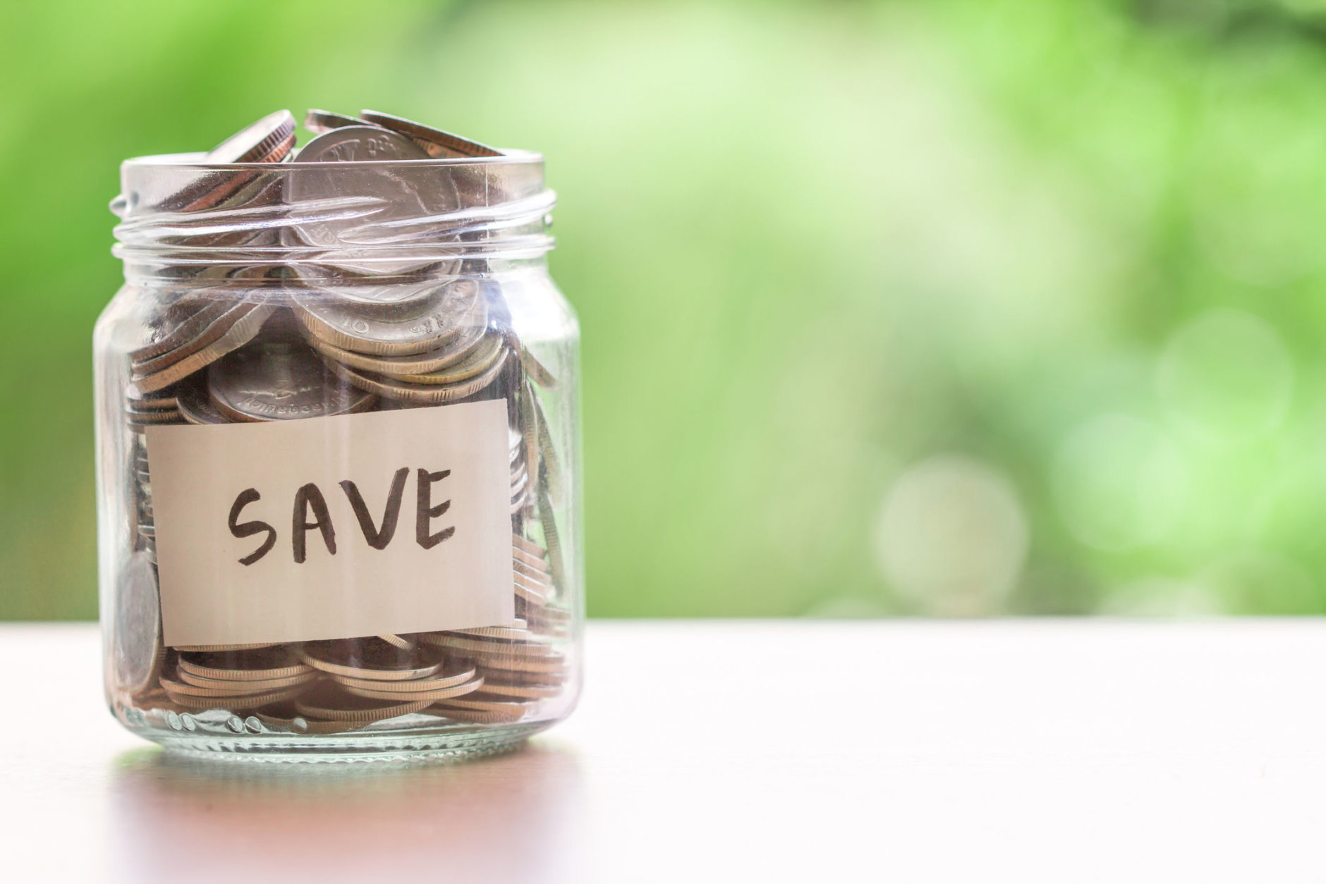 Coins in glass jar for money saving financial concept