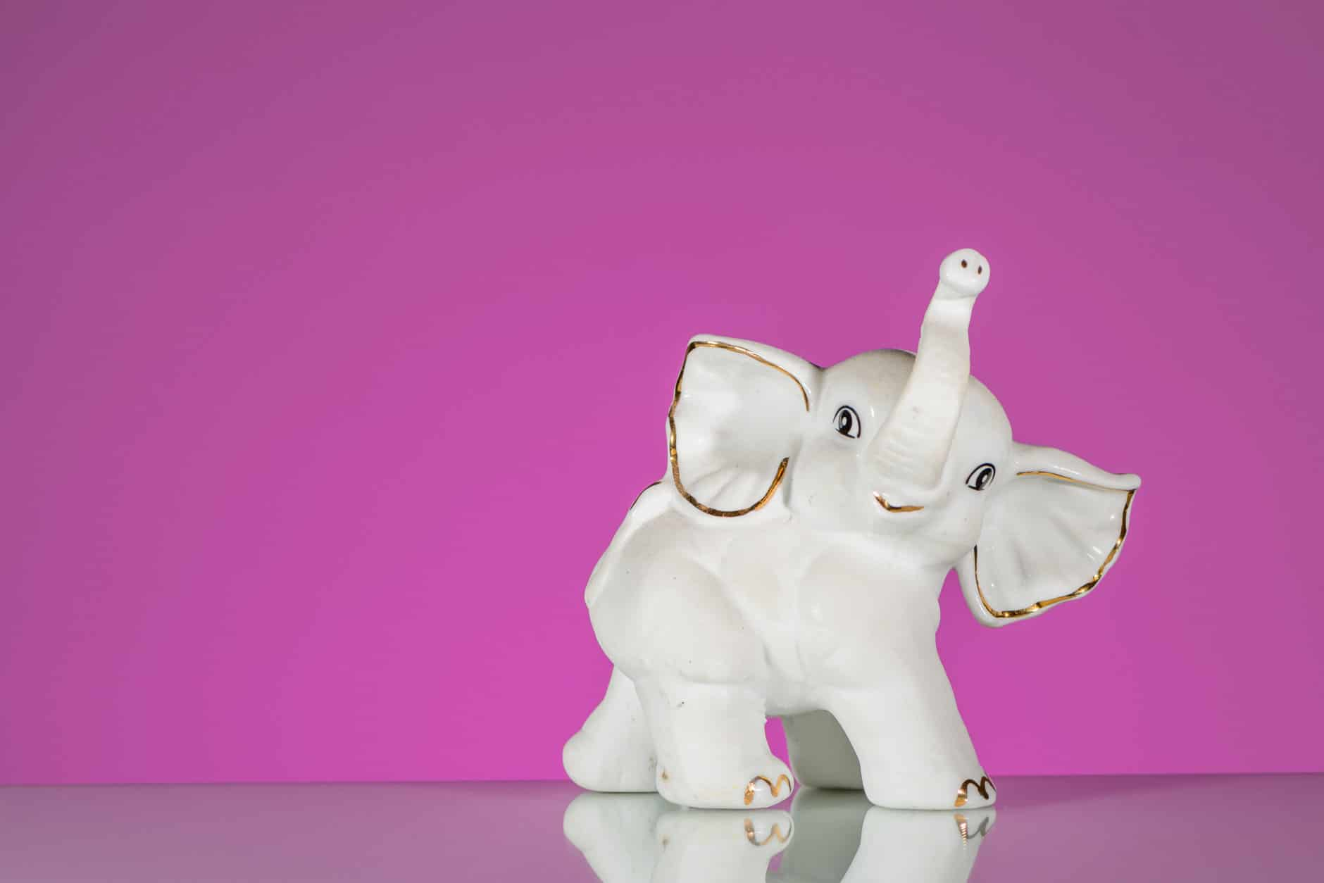 Closeup of white elephant made of porcelain, pink background