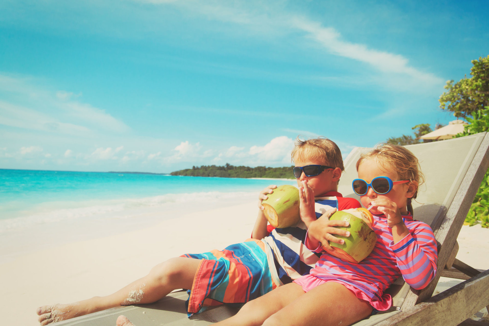 little boy and girl drinking coconut on tropical beach