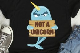 """This photo released by FreshDressedTees shows a black T-shirt with a grumpy blue narwhal holding a sign reading: """"Not a Unicorn."""" The shirt is sold on Etsy.com by the shop FreshDressedTees. Narwhals have become a popular """"it"""" creature on a range of items in time for the holiday shopping season. (AP Photo/FreshDressedTees)"""
