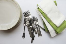This November 2015 photo taken in New York City provided by Katie Workman shows napkins, forks and plates on a table in New York. Setting up as much as you can for a party the night before is key. Whatever you can take out and leave out — dishes, napkins, glasses, platters — means less frantic last minute activity the day of. (Laura Agra/Katie Workman via AP)