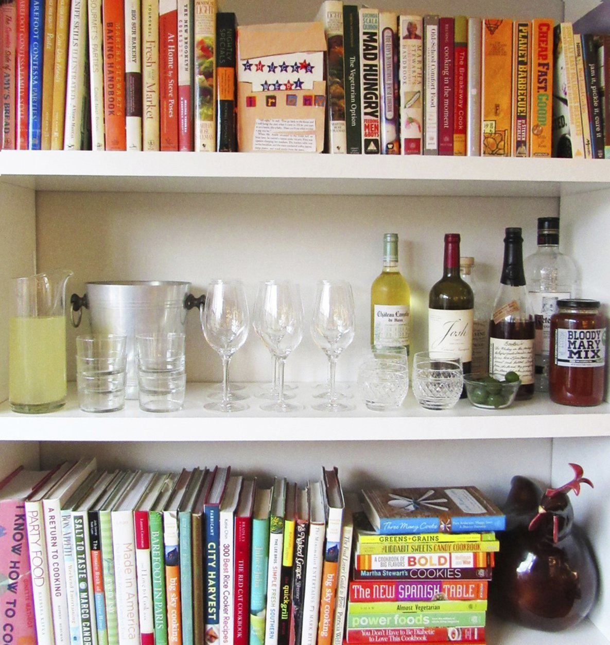This November 2015 photo provided by Katie Workman shows a temporary bar for a party being set up in a bookcase in New York. Making the most of different areas of your home is very helpful when you have a big group over. (Laura Agra/Katie Workman via AP)