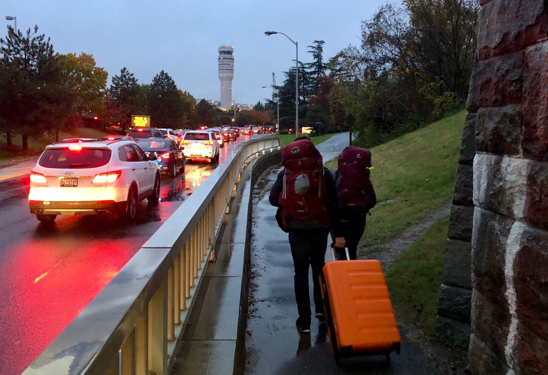 Travelers bailing out of cars on foot and rushing to departures dragging suitcases behind (WTOP/Dave Dildine)