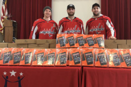 The Washington Capitals' Nicklas Backstrom, Braden Holtby and Tom Wilson presents the gifts of tablets and laptops to a Southeast D.C. elementary school. There was also the added gift of a room makeover. (WTOP/Kristi King)