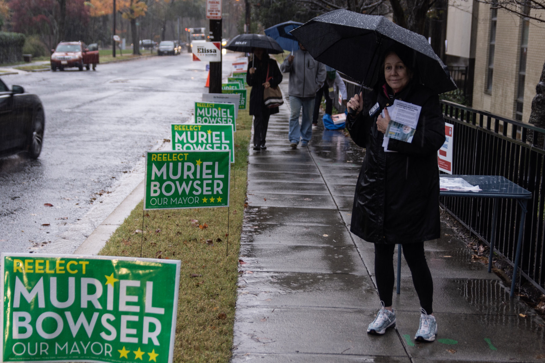 Signs for local candidates compete for space on the sidewalk as voters arrive at the Washington Hebrew Congregation in Northwest D.C. (WTOP/Alejandro Alvarez)