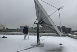 WTOP's Chris Cichon hits the roof at WTOP to clean off the satellite dish. (WTOP/Nahal Amouzadeh)
