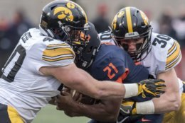 Iowa's Parker Hesse (40) and Jake Gervase (30) tackle Illinois' Ra'Von Bonner (21) in the first half of a NCAA college football game, Saturday, Nov. 17, 2018, in Champaign, Ill. (AP Photo/Holly Hart)