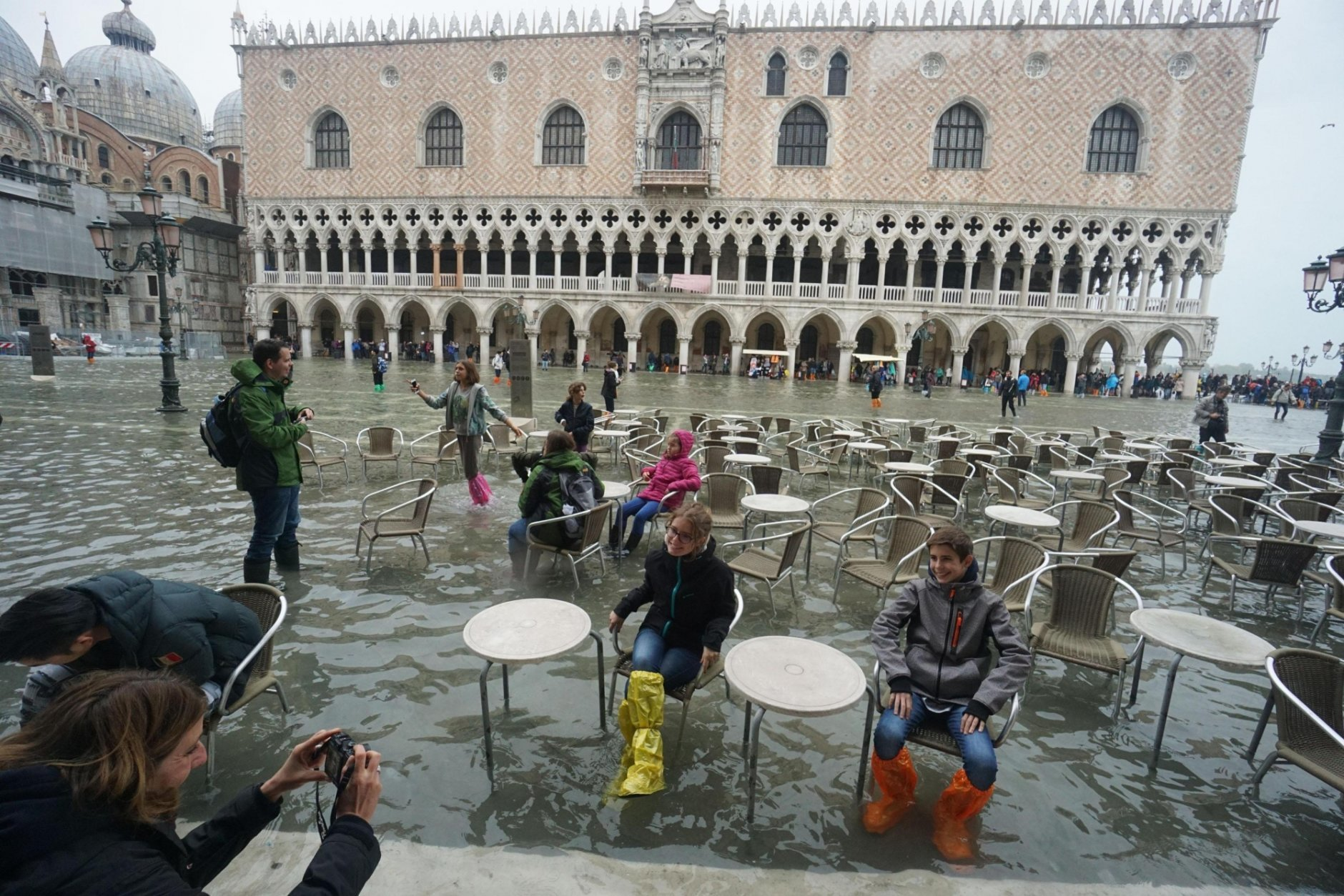 Tourists pose for a selfie in flooded St. Mark's Square in Venice, Italy, Thursday, Nov. 1, 2018 as rainstorms and strong winds have been battering the country. Two people were killed when a falling tree crushed their car in the mountainous countryside in northwestern Italy, as rainstorms and strong winds continued to pummel much of the country. (Andrea Merola/ANSA via AP)