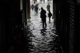 Tourists walk in flooded St. Mark's Square in Venice, Italy, Thursday, Nov. 1, 2018 as rainstorms and strong winds have been battering the country. Two people were killed when a falling tree crushed their car in the mountainous countryside in northwestern Italy, as rainstorms and strong winds continued to pummel much of the country. (AP Photo/Luca Bruno)