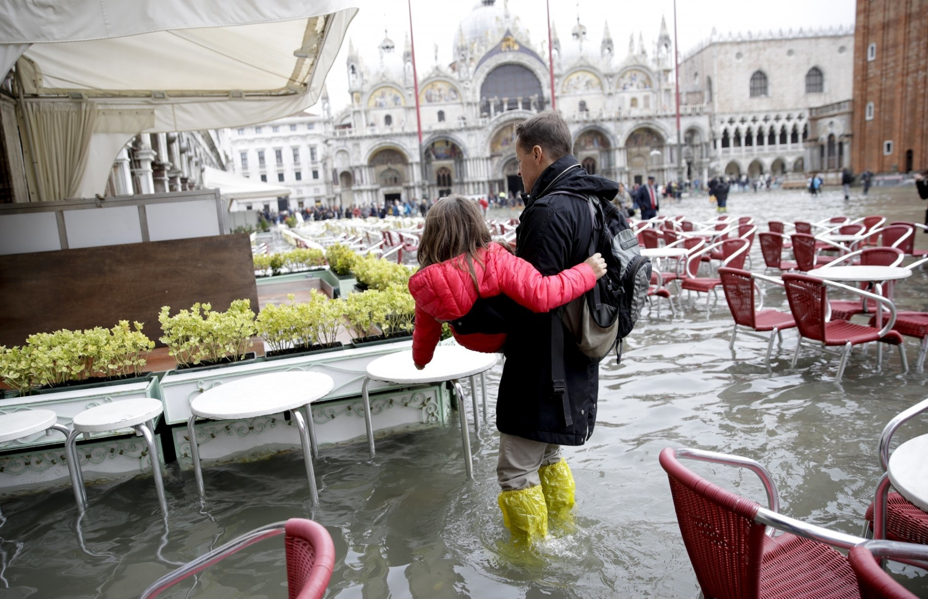 A man holds a girl as they walk in flooded St. Mark's Square in Venice, Italy, Thursday, Nov. 1, 2018 as rainstorms and strong winds have been battering the country. Two people were killed when a falling tree crushed their car in the mountainous countryside in northwestern Italy, as rainstorms and strong winds continued to pummel much of the country. (AP Photo/Luca Bruno)
