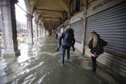 Tourists make their way through flooded St. Mark's Square in Venice, Italy, Thursday, Nov. 1, 2018 as rainstorms and strong winds have been battering the country. Two people were killed when a falling tree crushed their car in the mountainous countryside in northwestern Italy, as rainstorms and strong winds continued to pummel much of the country. (AP Photo/Luca Bruno)