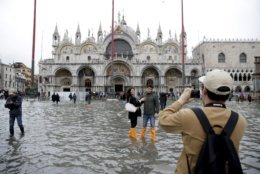 Tourists pose for photos in flooded St. Mark's Square in Venice, Italy, Thursday, Nov. 1, 2018 as rainstorms and strong winds have been battering the country. Two people were killed when a falling tree crushed their car in the mountainous countryside in northwestern Italy, as rainstorms and strong winds continued to pummel much of the country. (AP Photo/Luca Bruno)