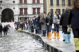 Tourists walk on wooden platforms in flooded St. Mark's Square in Venice, Italy, Thursday, Nov. 1, 2018 as rainstorms and strong winds have been battering the country. Two people were killed when a falling tree crushed their car in the mountainous countryside in northwestern Italy, as rainstorms and strong winds continued to pummel much of the country. (AP Photo/Luca Bruno)