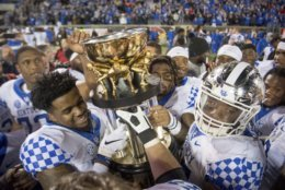 Kentucky players hoist the Governor's Cup after a 56-10 win over Louisville in an NCAA college football game  in Louisville, Ky., Saturday, Nov. 24, 2018. (AP Photo/Bryan Woolston)