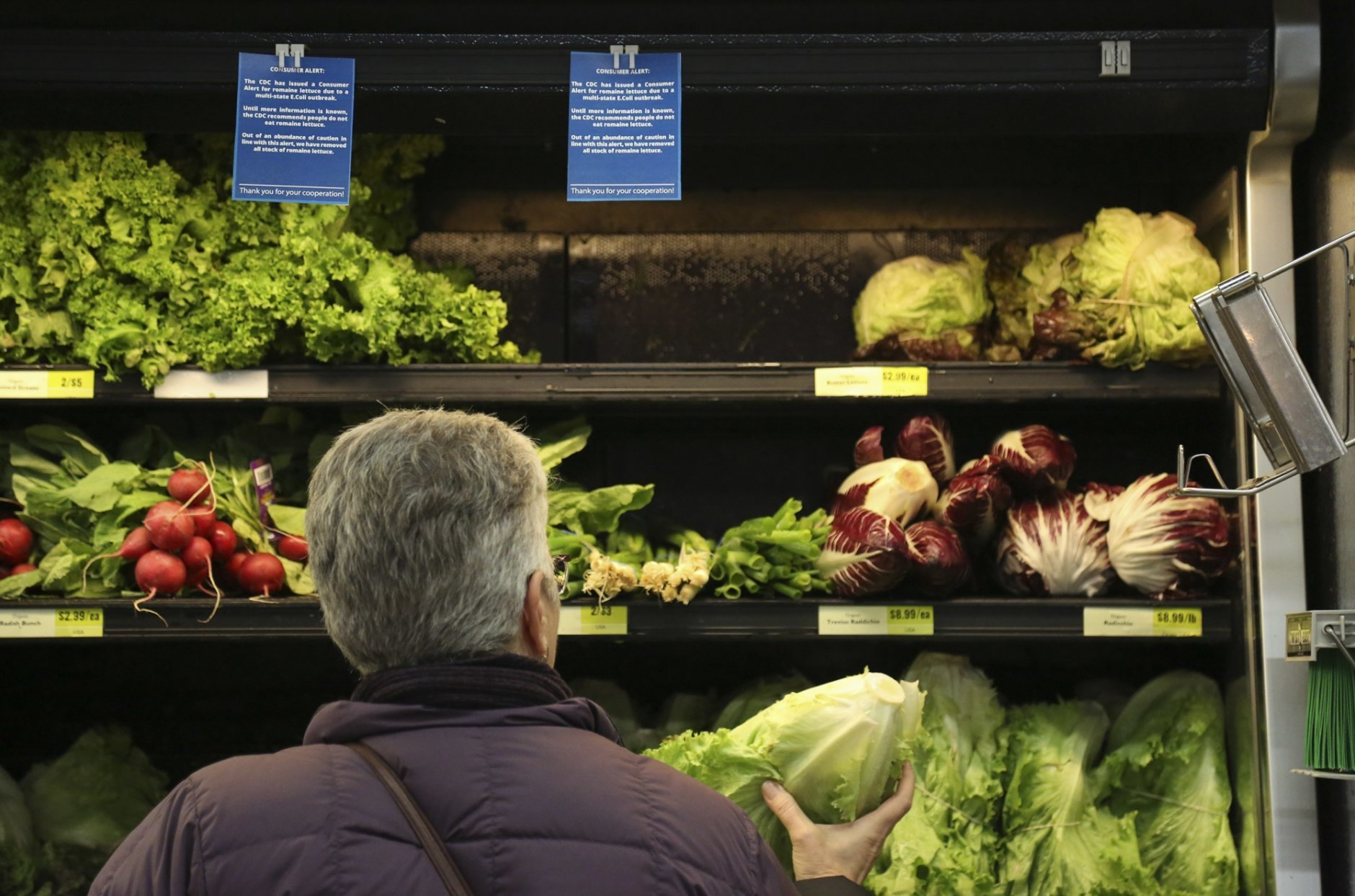 """Lisa Dennis of Regent Square selects a head of green lettuce from the vegetable shelves at the East End Food Co-op Federal Credit Union Tuesday, Nov. 20, 2018, in Pittsburgh. Due to a recent consumer alert regarding a multi state E.Coli outbreak the Co-op has replaced their fresh and bagged romaine lettuce with blue signs reading, """"The CDC has issued a Consumer Alert for romaine lettuce due to a multi state E.Coli outbreak."""" (Jessie Wardarski/Pittsburgh Post-Gazette via AP)"""