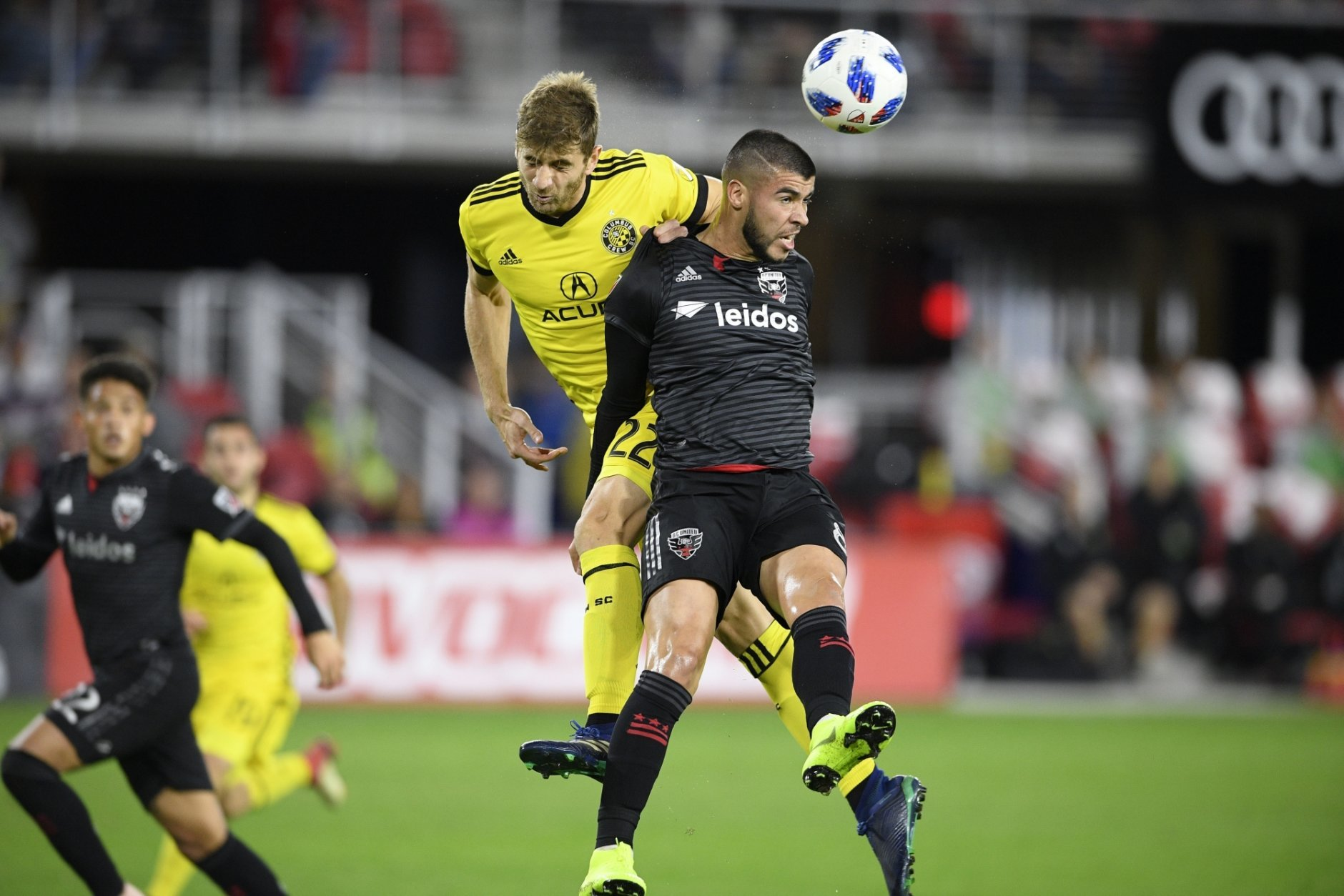 D.C. United midfielder Ulises Segura, front, battles for the ball against Columbus Crew SC defender Gaston Sauro (22) during the first half of an MLS playoff soccer match, Thursday, Nov. 1, 2018, in Washington. (AP Photo/Nick Wass)