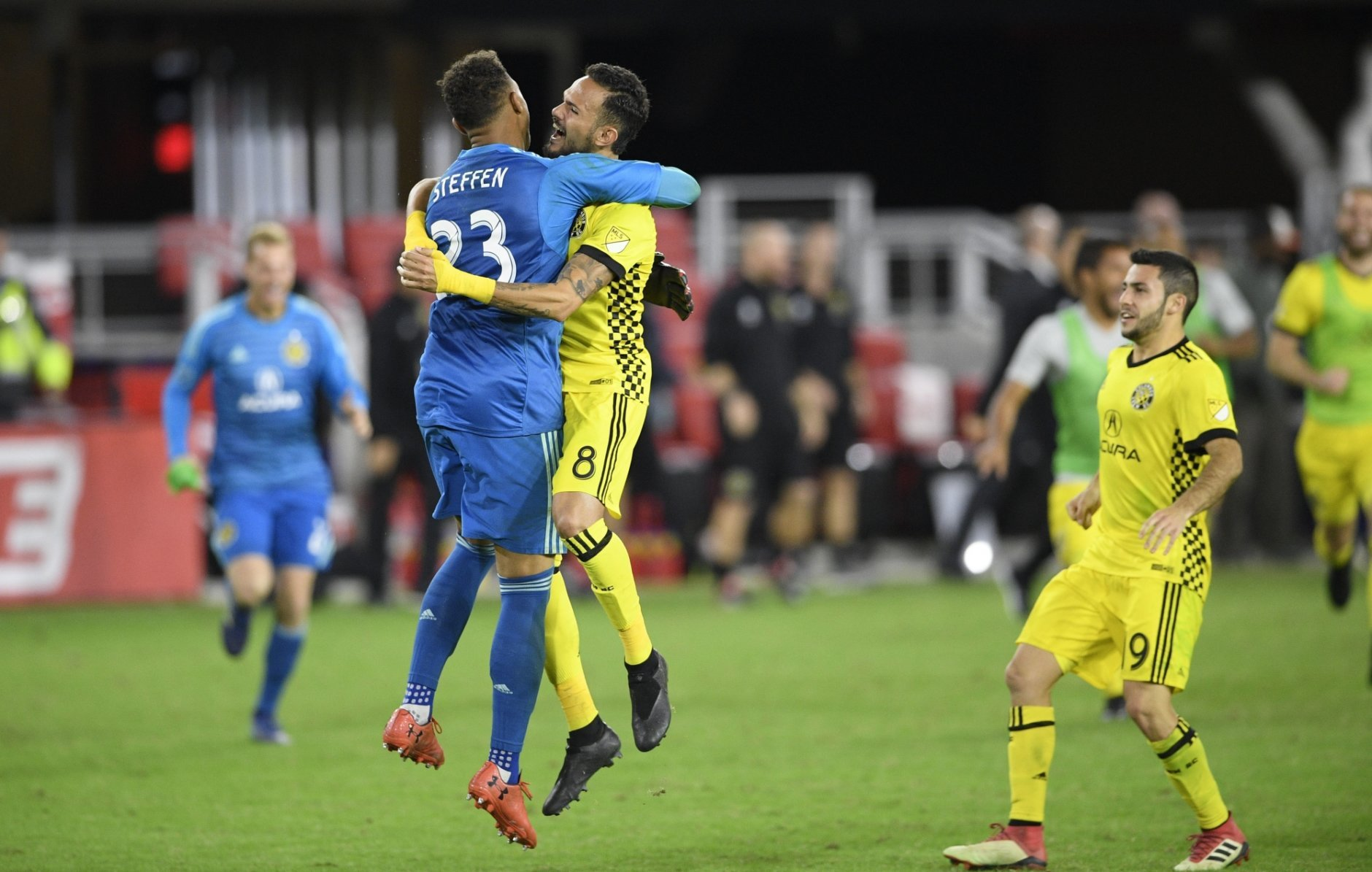Columbus Crew SC goalkeeper Zack Steffen (23) celebrates with midfielder Artur (8) and defender Milton Valenzuela, right, after winning an MLS playoff soccer match in penalty kicks against D.C. United, Thursday, Nov. 1, 2018, in Washington. The Crew SC won 2-2 (3-2) in penalty kicks. (AP Photo/Nick Wass)