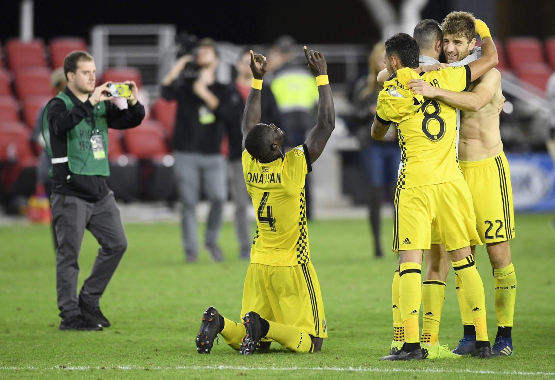 Columbus Crew SC defender Jonathan Mensah (4), midfielder Artur (8) and defender Gaston Sauro (22) celebrate after winning an MLS playoff soccer match in penalty kicks against D.C. United, Thursday, Nov. 1, 2018, in Washington. The Crew SC won 2-2 (3-2) in penalty kicks. (AP Photo/Nick Wass)