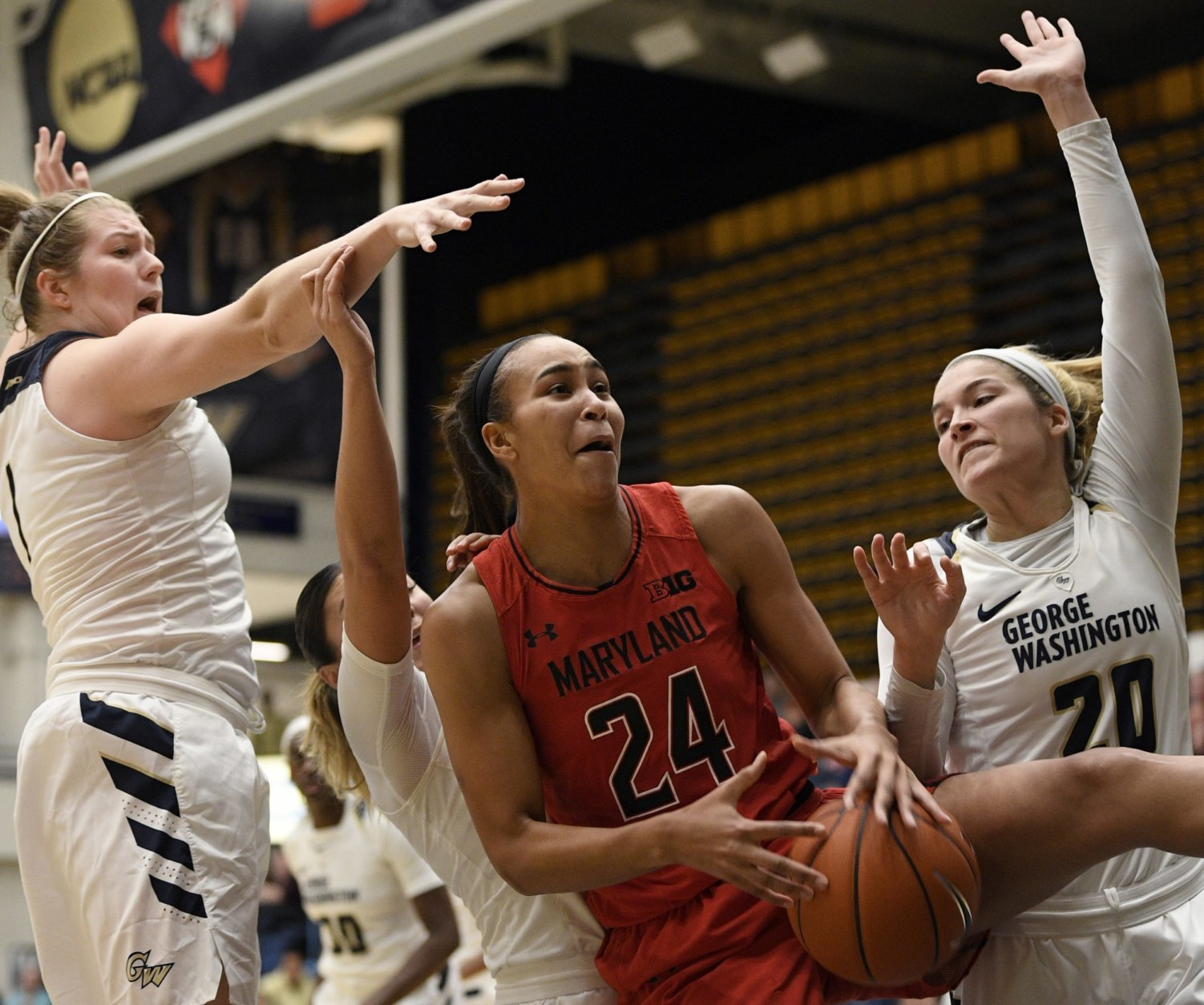 George Washington forward Kelsi Mahoney (1) and forward Sarah Overcash (20) defend against Maryland forward Stephanie Jones (24) during the second half of an NCAA college basketball game, Wednesday, Nov. 14, 2018, in Washington. Maryland won 69-30. (AP Photo/Nick Wass)