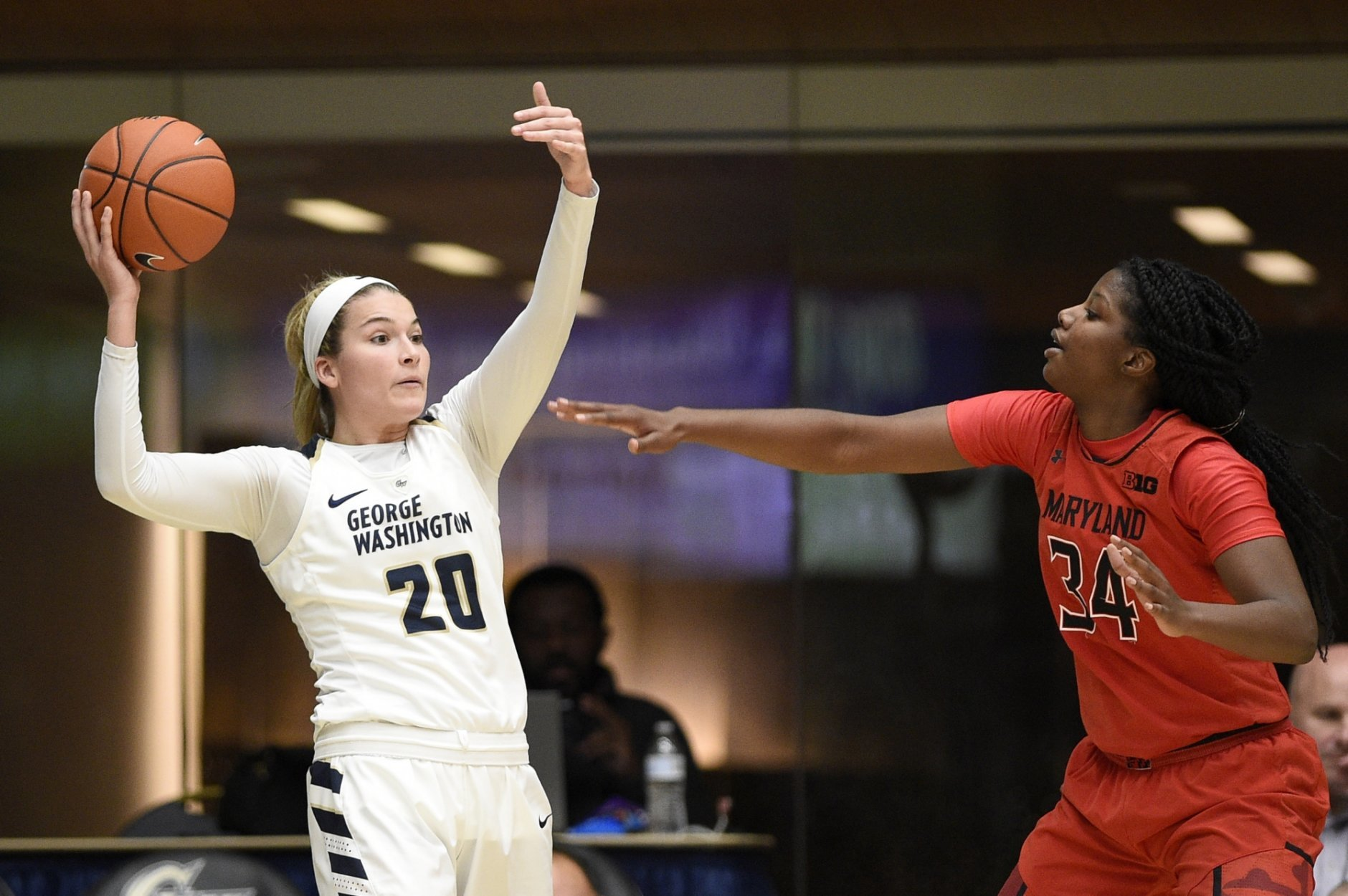 George Washington forward Sarah Overcash (20) holds the ball against Maryland forward Brianna Fraser (34) during the second half of an NCAA college basketball game, Wednesday, Nov. 14, 2018, in Washington. Maryland won 69-30. (AP Photo/Nick Wass)