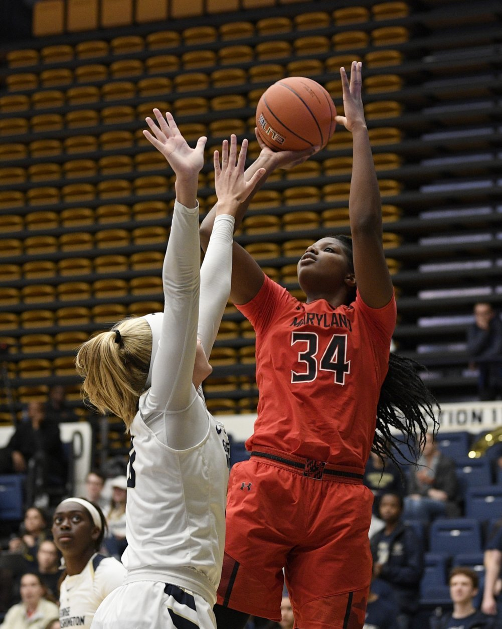 Maryland forward Brianna Fraser (34) shoots against George Washington forward Sarah Overcash, left, during the second half of an NCAA college basketball game, Wednesday, Nov. 14, 2018, in Washington. Maryland won 69-30. (AP Photo/Nick Wass)