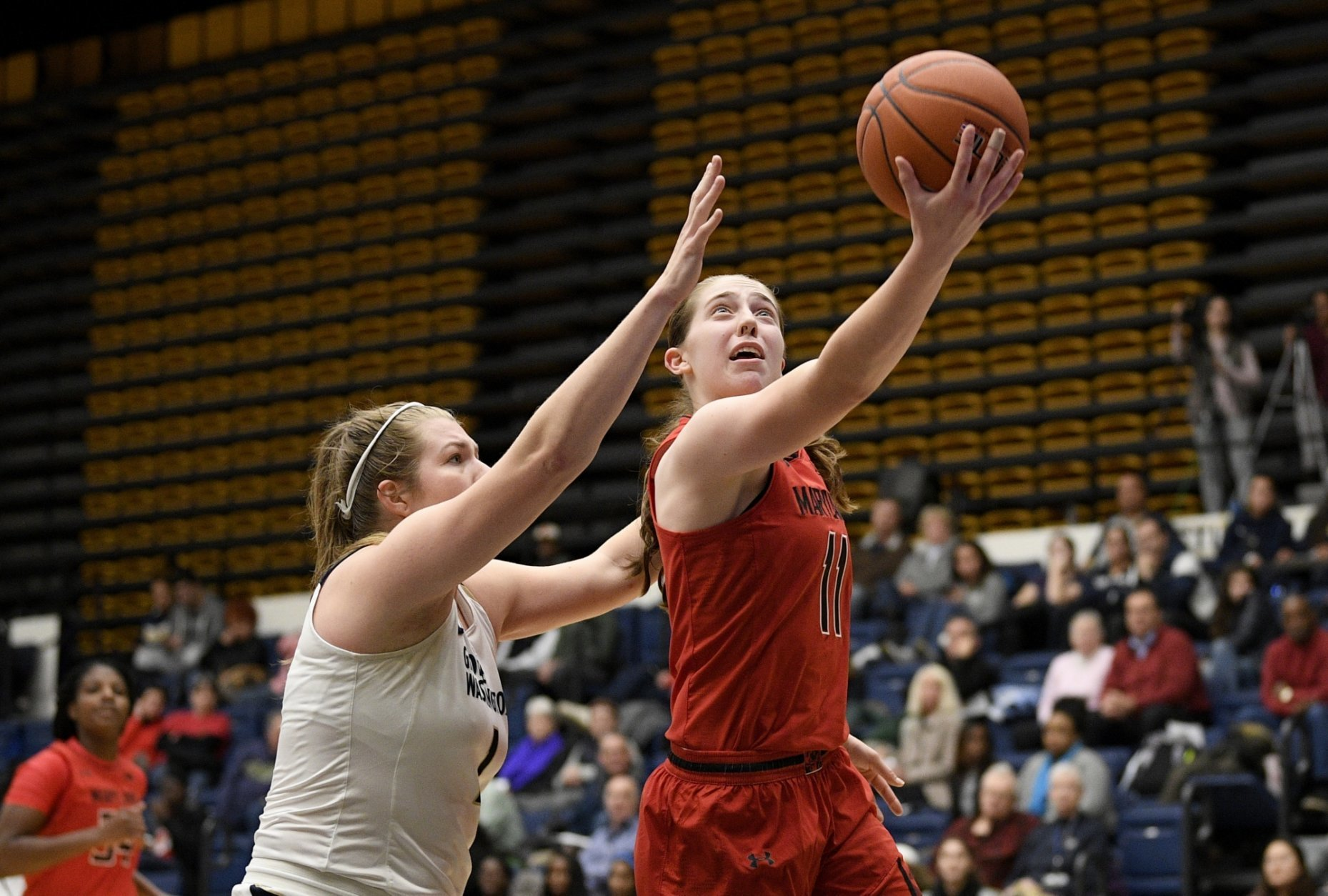 Maryland guard Taylor Mikesell (11) goes to the basket past George Washington forward Kelsi Mahoney, left, during the second half of an NCAA college basketball game, Wednesday, Nov. 14, 2018, in Washington. Maryland won 69-30. (AP Photo/Nick Wass)