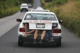 Central American migrants, part of the caravan hoping to reach the U.S. border, a ride on in the trunk of a taxi, in Acayucan, Veracruz state, Mexico, Saturday, Nov. 3, 2018. (AP Photo / Marco Ugarte)