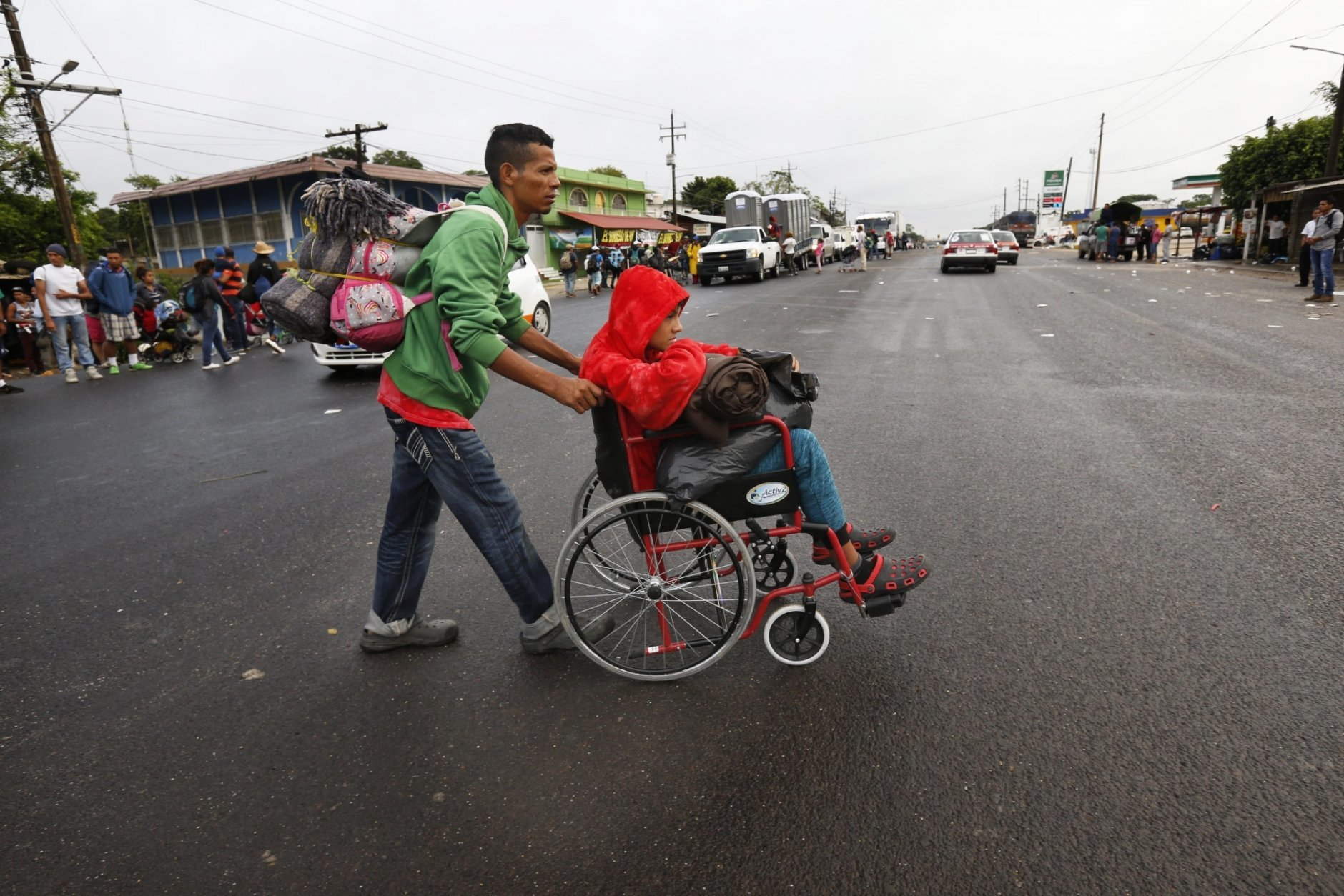 Nicaraguan migrant Javier Velazquez wheels his 14-year-old son across the highway, as part of the Central American migrant caravan hoping to reach the U.S. border, in Acayucan, Veracruz state, Mexico, Saturday, Nov. 3, 2018. Javier Velazquez  said that Axel was shot in the leg during protests in Nicaragua and both are looking for political asylum in the United States. (AP Photo / Marco Ugarte)