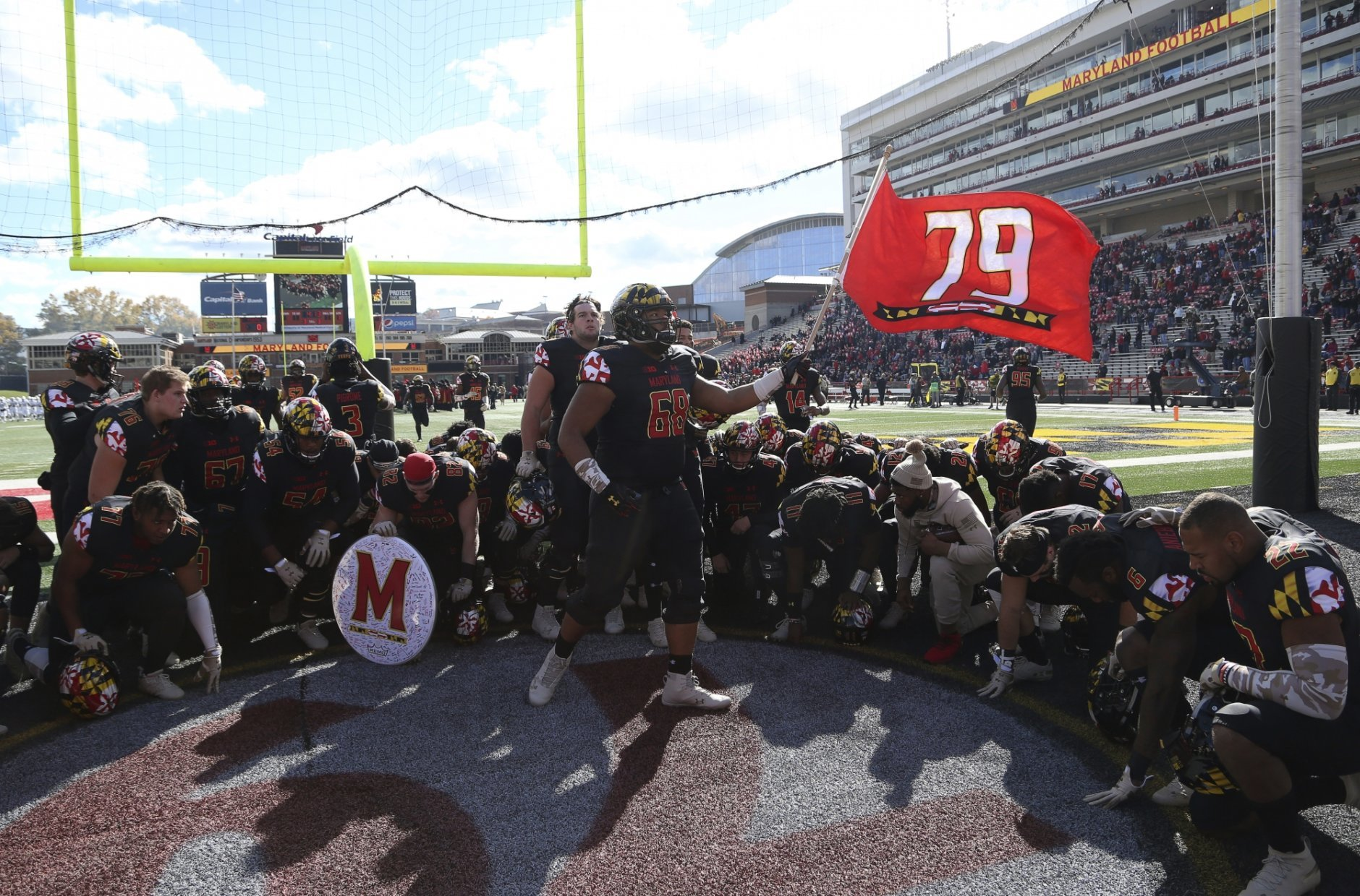 Maryland players kneel and honor their deceased teammate Jordan McNair (79) before an NCAA college football game against Michigan State, Saturday, Nov. 3, 2018, in College Park, Md. (AP Photo/Gary Cameron)