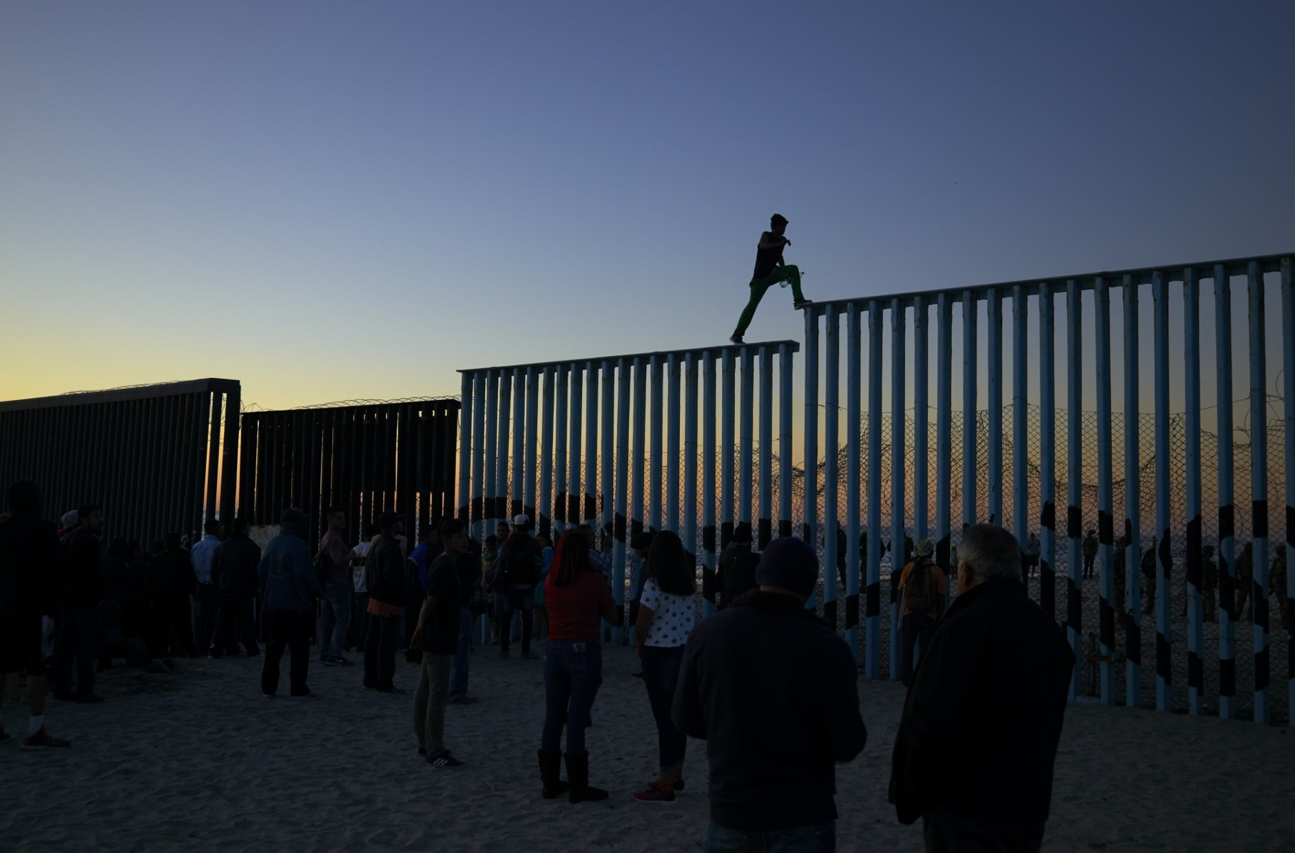 In this Nov. 14, 2018 picture, a man from Honduras walks along the top of the border structure separating Mexico and the United States, in Tijuana, Mexico. With about 3,000 Central American migrants having reached the Mexican border across from California and thousands more anticipated, the city of Tijuana continues to prepare for an influx that will last at least six months and may have no end in sight. (AP Photo/Gregory Bull)